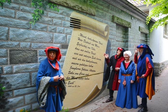 Vier Darsteller des Mittelalterfestivals vor einem Wandgemälde des Soester Fehde Dokuments.