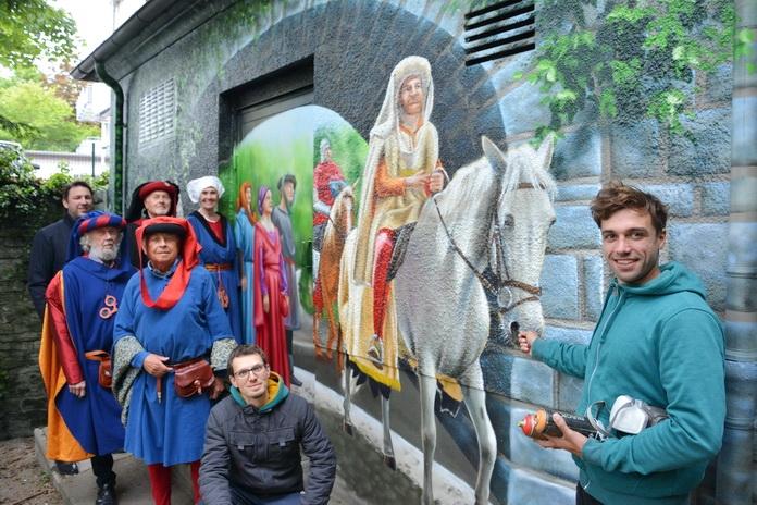 Wandgemälde auf einer Trafostation der Stadtwerke, eine Szene der Soester Fehde. Im Vordergrund stehen die beiden Künstler, Darsteller des Mittelalterfestivals und der Geschäftsführer der Stadtwerke.